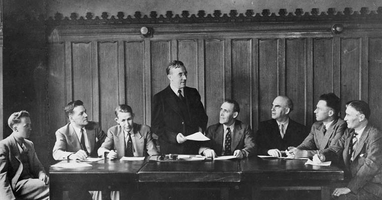 Federal CCF Caucus, 1942. M.J. Coldwell is the new leader after Woodsworth's death. Left to right, Tommy Douglas, George Castleden, Angus MacInnis, Coldwell, Clarie Gillis , Joe Noseworthy, Sandy Nicholoson, and Percy Wright. Photo: C.C.F. / Library and Archives Canada / C-000314 via Wikimedia Commons
