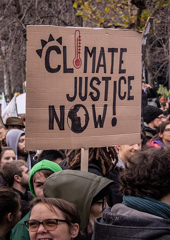 543px-Climate_Justice_Now!,_placard,_2018_(cropped)