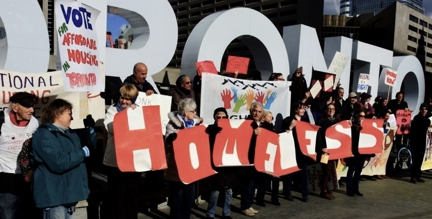 Protesters hold signs about homelessness in front of the Toronto sign at Toronto City Hall (Image: Photo by Cathy Crowe)