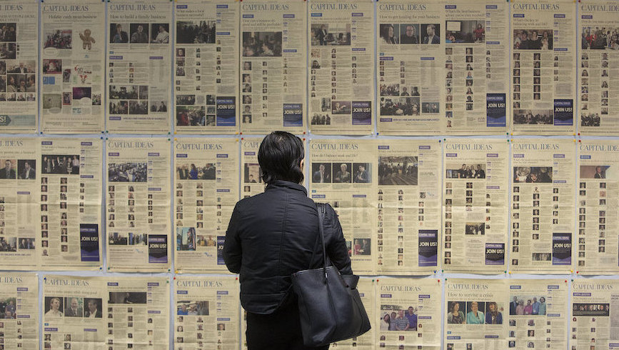 Person stands in front of display of newspaper broadsheets. Image credit: Jason Franson/ Postmedia via Capital Ideas Edmonton/Flickr