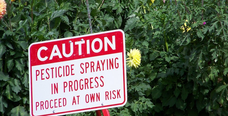 """A caution sign reads """"Pesticide spraying in progress. Proceed at own risk."""" Image credit: jetsandzeppelins/Flickr"""