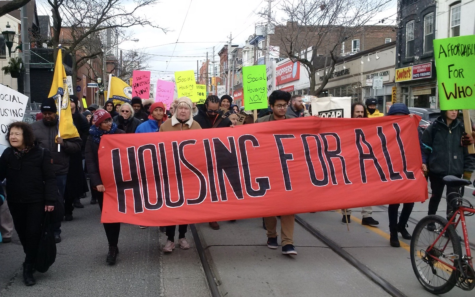 """Housing advocates carry a banner. Black words on red read, """"Housing for All."""" Many signs in background say """"Social Housing Now."""" Image: Cathy Crowe/Used with permission"""